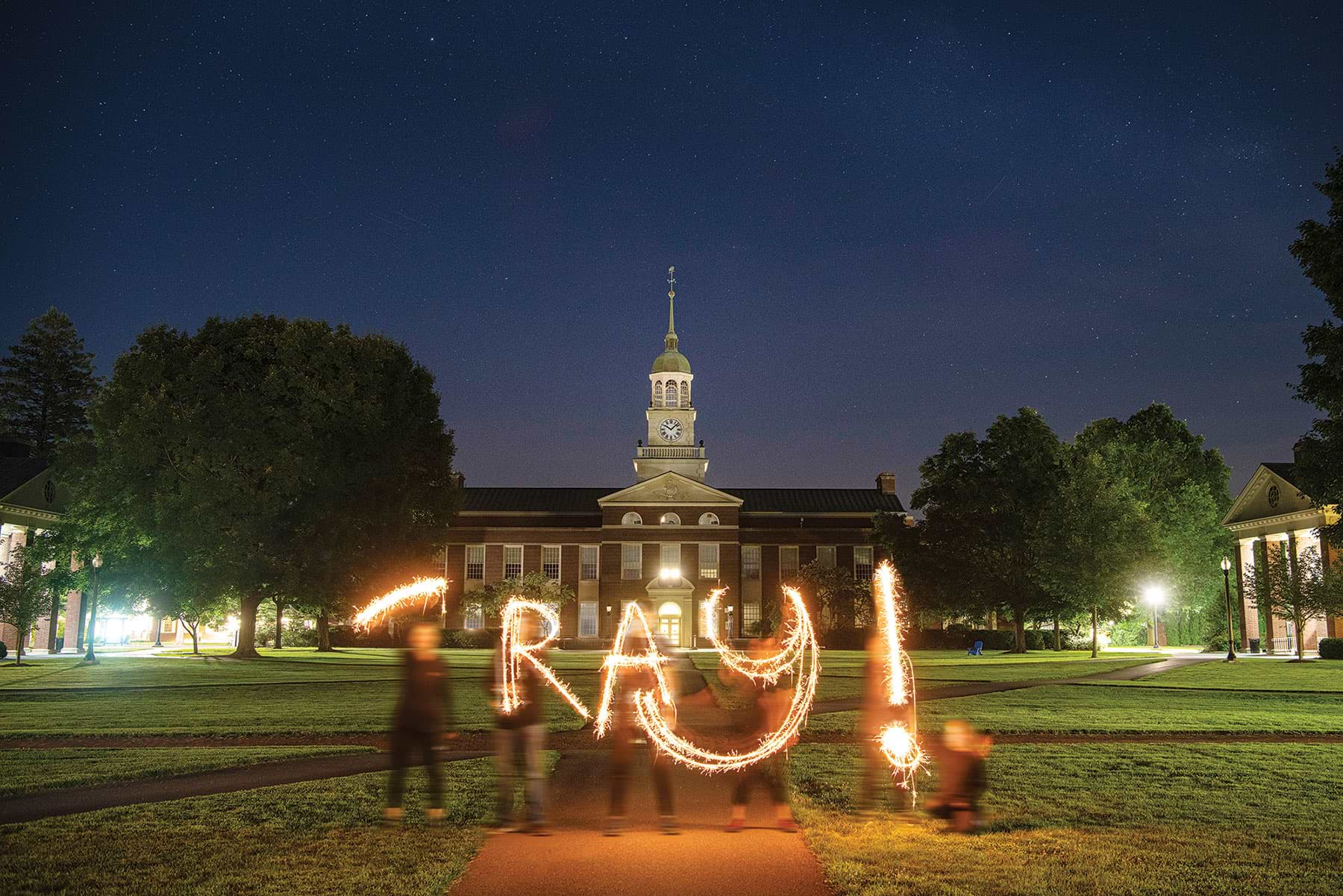 Students writing 'ray with light at night on campus