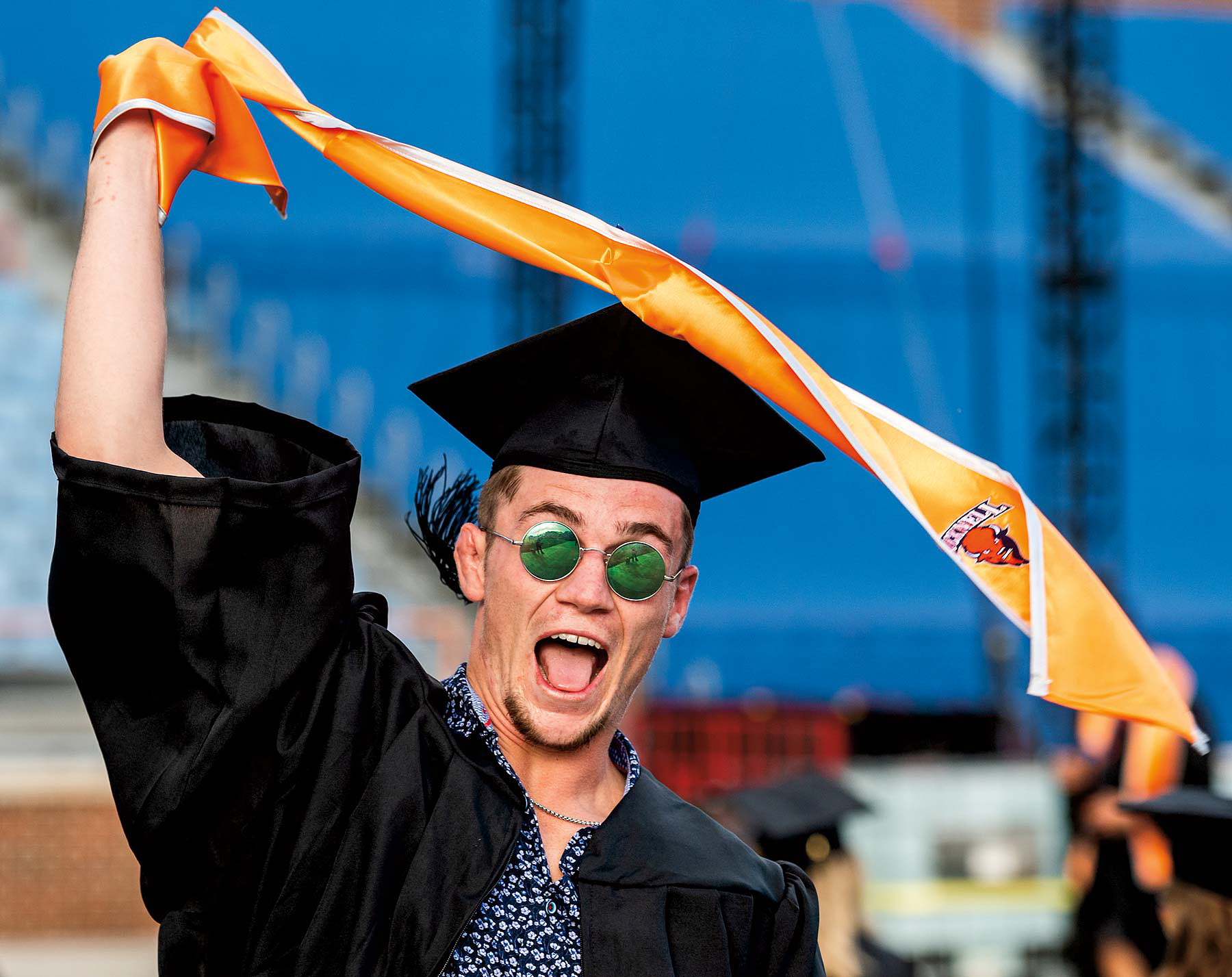 Graduate of Bucknell wearing a graduation cap and gown and green circular sunglasses celebrating happily