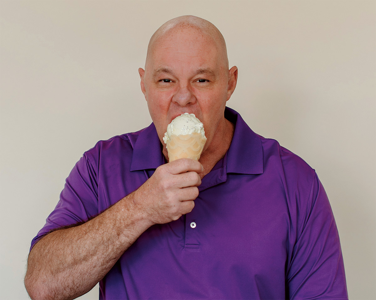 George Haymaker eating an ice cream cone in a purple polo shirt